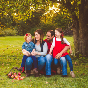 family of 4 in apple orchard in the fall laughing