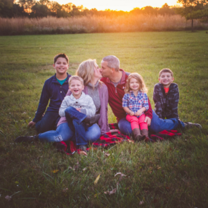 family of 6 sitting in meadow with sun setting in fall