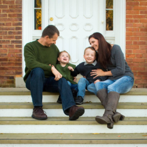 family of 4 sitting on steps of old building in new albany ohio