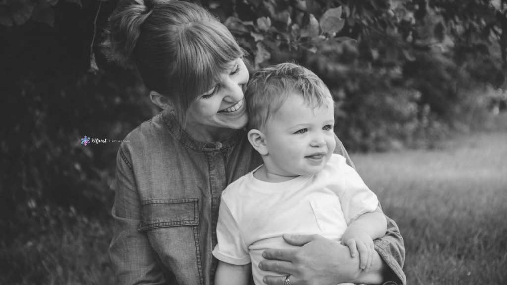 mom embracing young son on lap outside in front of apple tree
