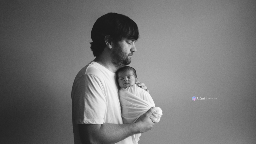 dad standing holding baby girl wrapped in white fabric facing in black and white image