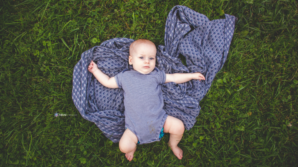 baby boy resting in grass with baby wrap