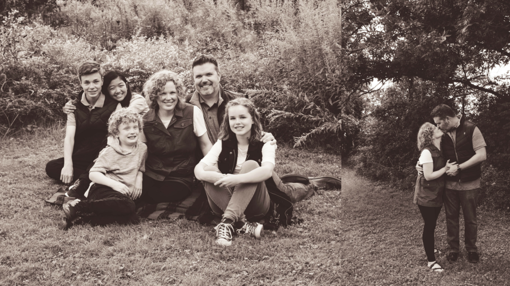 family of 6 sitting on ground smiling and mom and dad kissing eachother in black and white