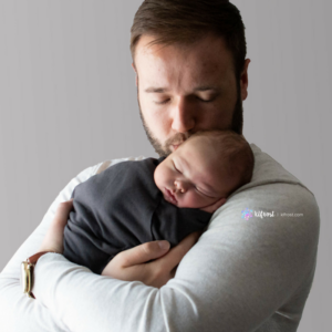 father kissing newborn son on head