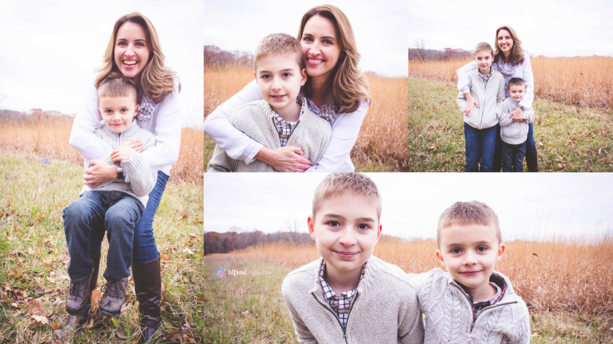 mother and sons playing in field wearing grey sweaters and blue jeans