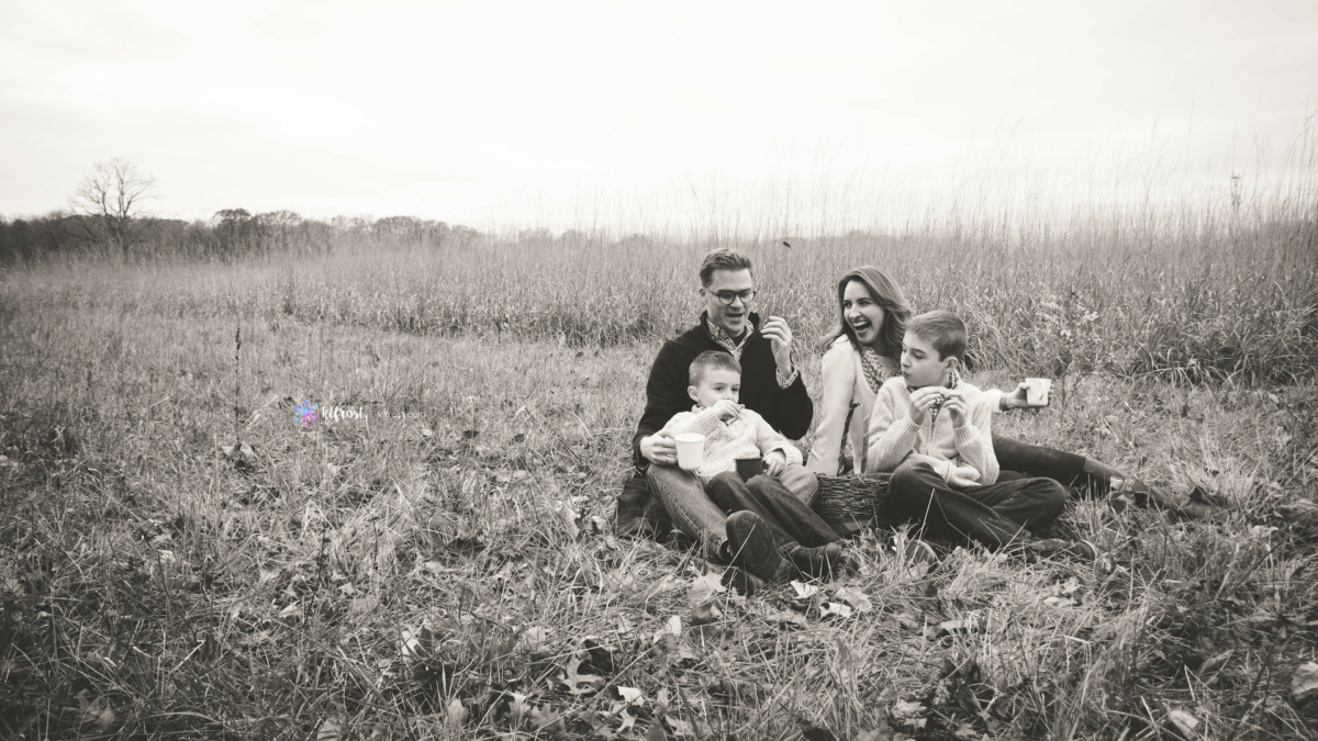 family of 4 drinking hot cocoa and laughing in field in black and white