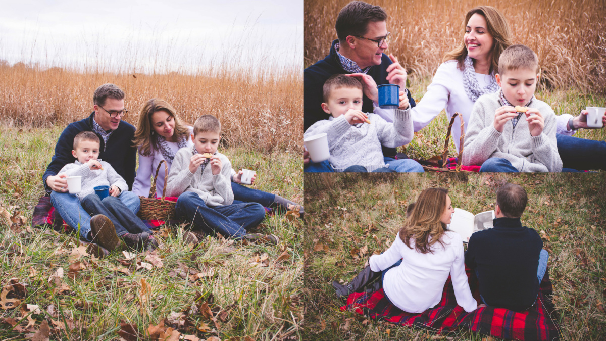 family of 4 sitting on red plaid blanket drinking hot cocoa and laughing