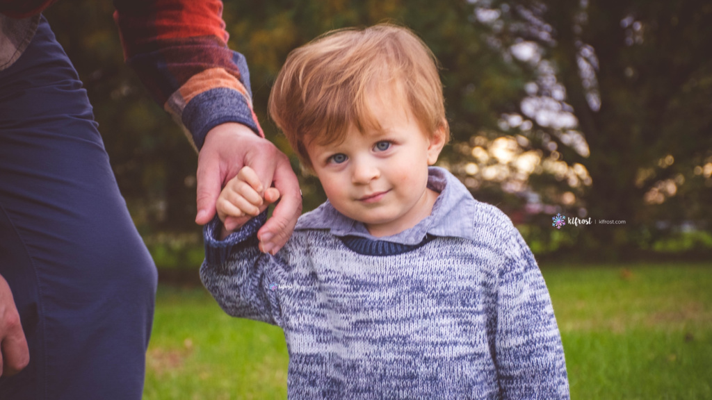 young boy holding dads hand with pine trees in background