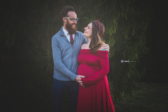 beautiful pregnant couple in red and grey embracing and smiling at each other