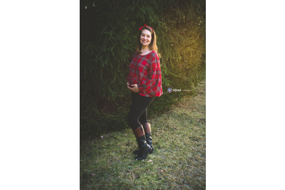beautiful pregnant woman in red plaid standing in front of giant pine tree holding baby belly