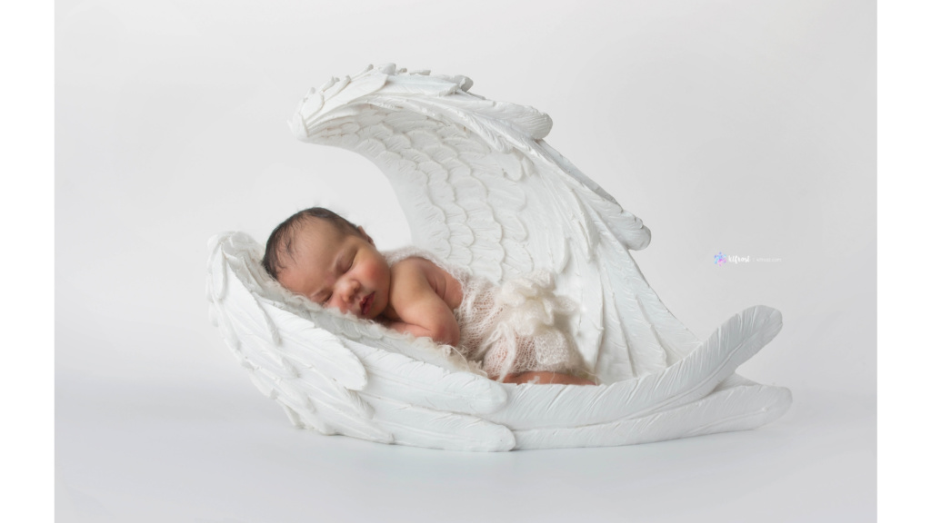 newborn baby asleep in white angel wings wearing white handmade white outfit