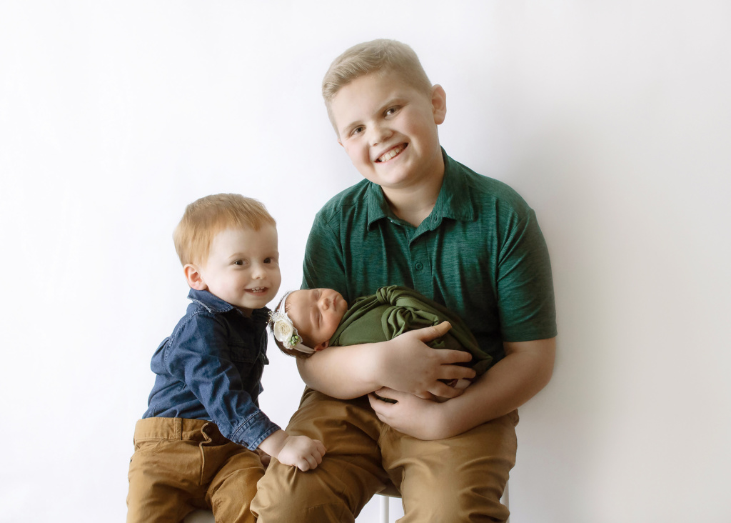 two older brothers in khaki, dark denim and forgest green holding their baby sister in olive