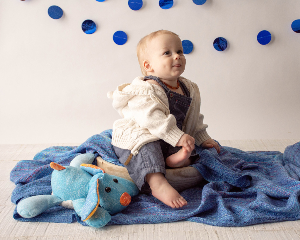 one year old boy at birthday photography session with blue dot embellishment on wall sitting on blue woven baby wrap with handmade puppy animal
