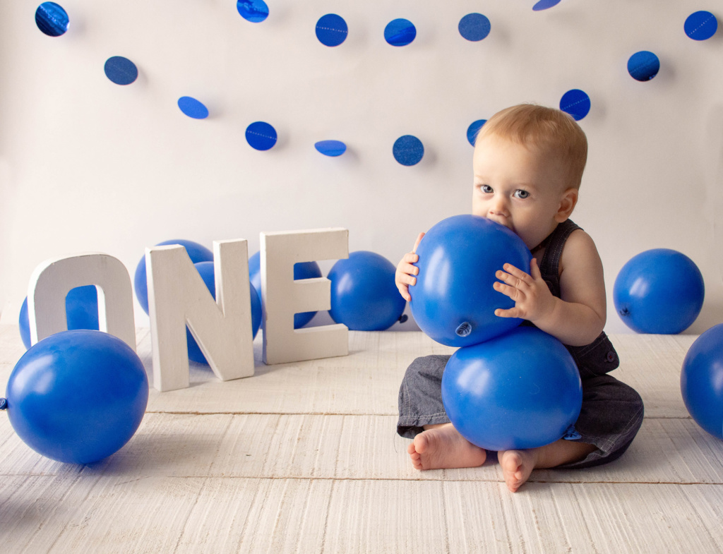 portrait of baby boy with blue balloons in front of letters spelling one