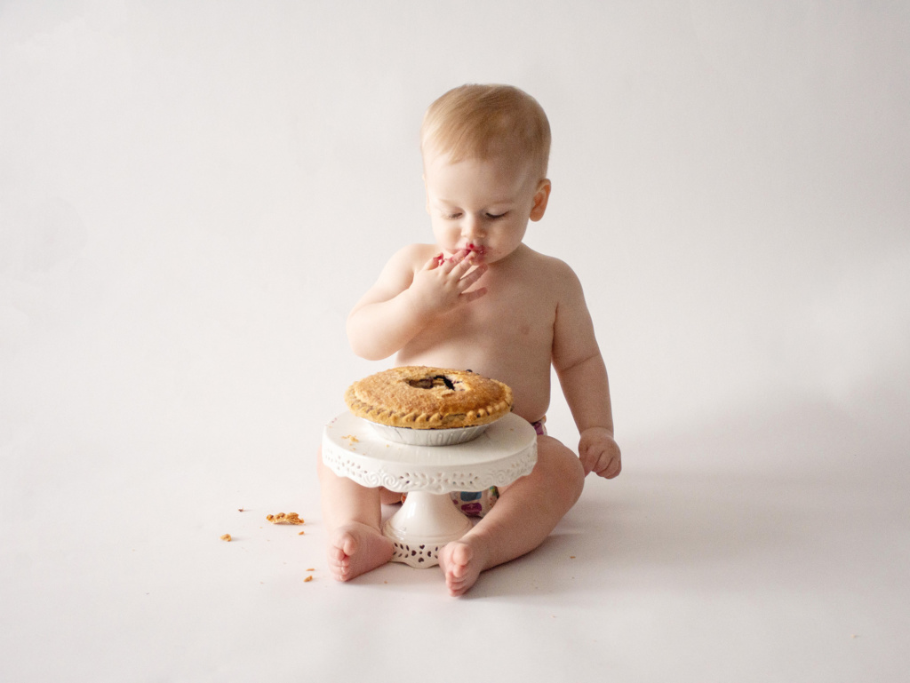 baby boy trying a blueberry pie at one year portrait session