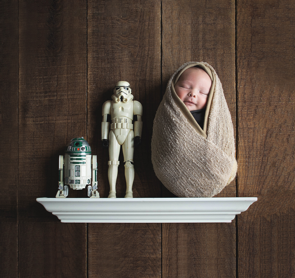 newborn baby boy in star wars portrait with vintage storm trooper and droid