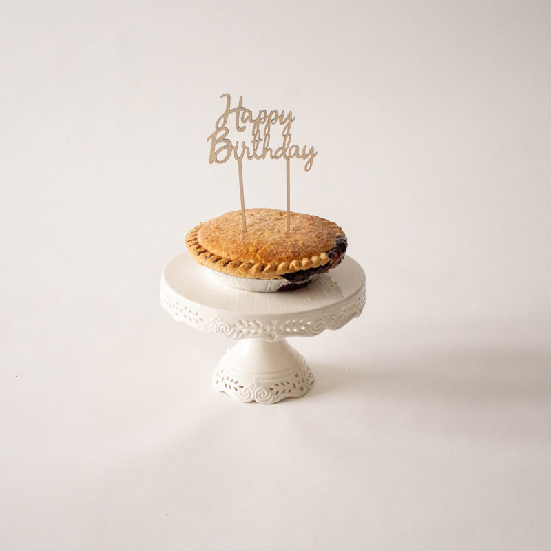blueberry pie on white porcelain stand with happy birthday sign in it